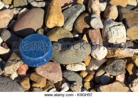 A cap from a single use bottle of water washed ashore and mixed with pebbles in Queensland, Australia. - Stock Photo