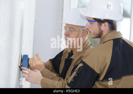 apprentice male builder sanding wall indoors - Stock Photo