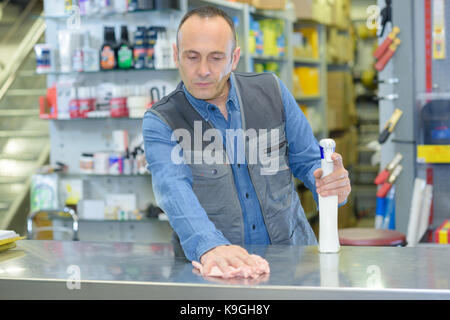 handsome hardware store worker cleaning counter with cloth - Stock Photo