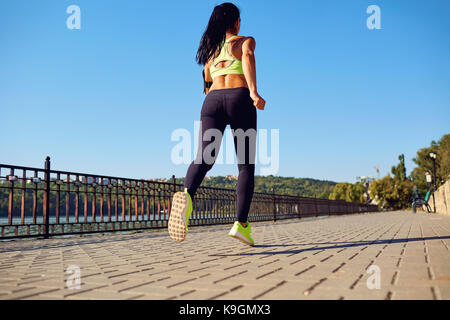 A sports girl runs through the park by the lake. - Stock Photo
