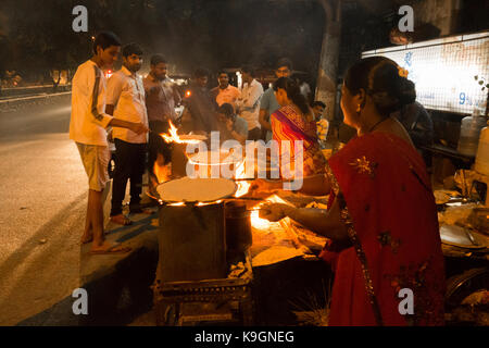 HYDERABAD,INDIA-22nd SEPTEMBER,2017.Indian women prepare Jowar Roti (Sorghum flour flat bread) on a wood fire cooking - Stock Photo