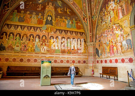 A woman admires the Triumph of the Catholic Doctrine by Andrea di Buonaiuto in the Spanish Chapel section of Santa - Stock Photo