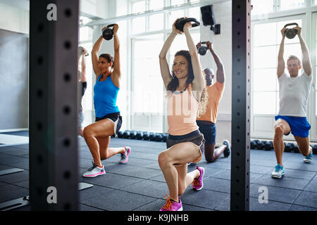 Smiling young woman doing lunges with weights while working out with a diverse group of people at the gym - Stock Photo