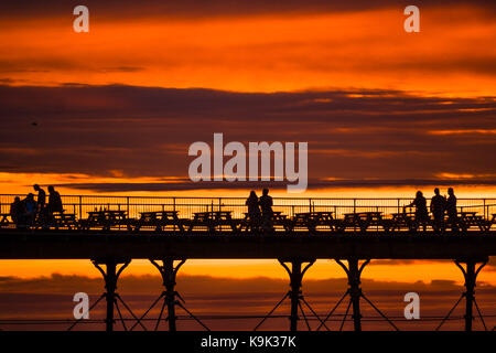 Aberystwyth Wales UK , Saturday 23 September 2017  UK Weather: People in silhouette watching a spectacular sunset - Stock Photo