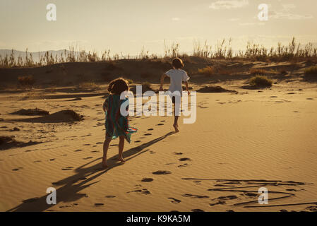 Boy and girl running wild on a sandy beach at sunset leaving footprints - Stock Photo