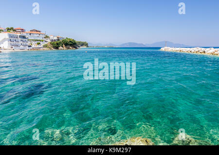 Rocky shallows with crystal clear water and beautiful settlement over blue sea. - Stock Photo