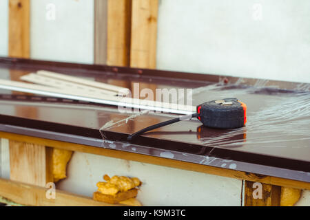 Attractive ... The Construction Tape Measure Rests On The Windowsill Outside The House    Stock Photo