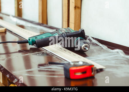 screwdriver lies next to the tape measure on the windowsill - Stock Photo