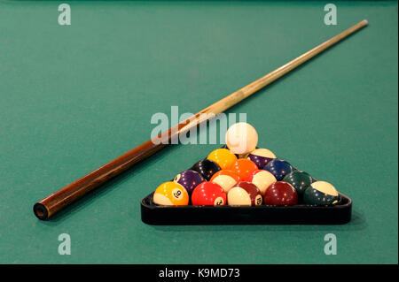 A cue stick and balls on a pool table - Stock Photo