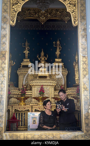 Whatchin the phone, women, believer, City Pillar Shrine, Bangkok, Thailand - Stock Photo