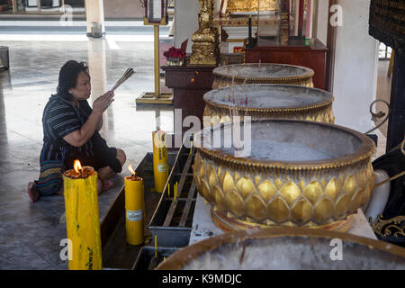 Woman praying, City Pillar Shrine, Bangkok, Thailand - Stock Photo