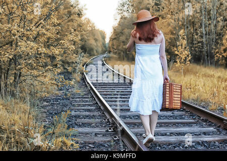 autumn park girl in white sundress and a wicker suitcase walking - Stock Photo