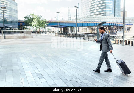 Businessman walking through the city with rolling suitcase and cell phone - Stock Photo