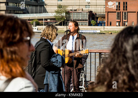 Street Performer or Busker on Bankside Southwark, London United Kingdom Entertaining a Crowd of People Against the - Stock Photo