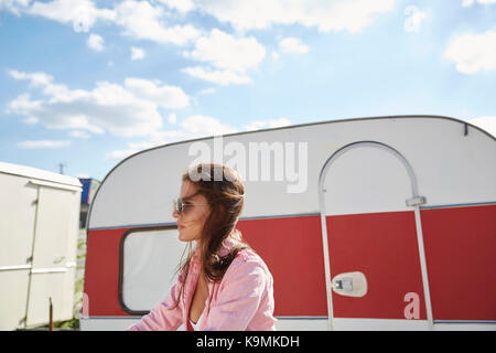 Young woman standing in front of food truck - Stock Photo