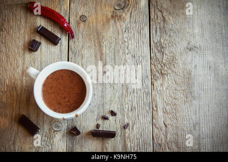 Hot Chocolate with chili pepper and chocolate pieces over rustic wooden background. Homemade Hot Chocolate Drink - Stock Photo