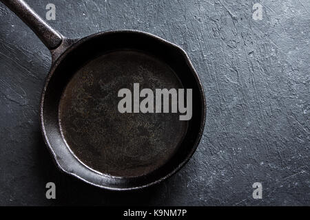 Cast iron pan on rustic black stone background close up -  empty black frying pan frying skillet with copy space - Stock Photo