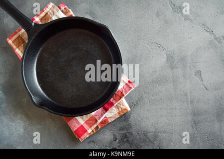 Cast iron pan on rustic grey concrete background close up -  empty black frying pan frying skillet with copy space - Stock Photo