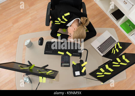 Tired Young Businesswoman With Reminder Notes Sleeping On Desk In Office - Stock Photo