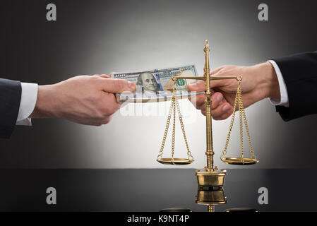 Close-up Of A Businessman Taking Bribe In Front Of Justice Scale - Stock Photo