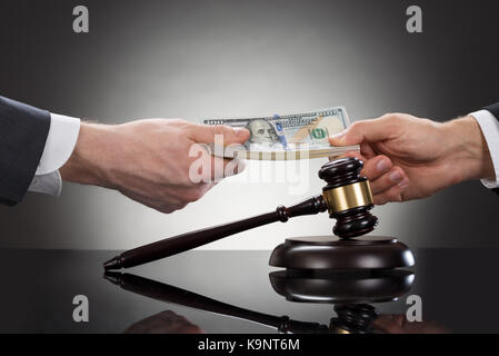 Close-up Of A Businessman Taking Bribe In Front Of Mallet - Stock Photo