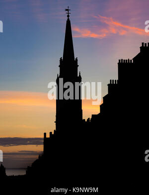 Colourful sunrise on Edinburgh's Royal Mile, with the silhouettes of the Tron Kirk and other rooflines visible in - Stock Photo