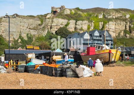 Artists on Hastings Stade Old Town beach drawing the fishing boats, East Sussex, England, UK - Stock Photo