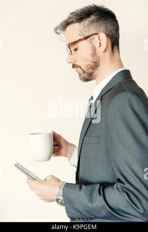 Side profile view portrait of professional businessman holding mobile phone and coffee mug wearing eye glasses. - Stock Photo