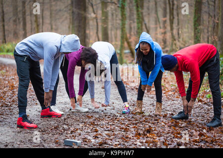 Young group of people warming up the upper-body outdoors - Stock Photo