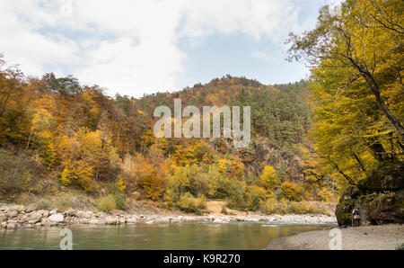 silent, perfection of nature, season concept. at the foot of rocky hills with autumn forests of fire colour there - Stock Photo