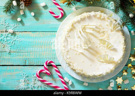 Holiday cake with icing white chocolate on festive christmas background. - Stock Photo