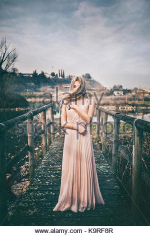 Portrait of a girl standing near a pond. Hair is moving. Blonde hair. Dreamy looks. Pastel colors. Light pink dress. - Stock Photo