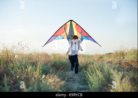fast little boy runs across the field with colorful kite in his hands over his head