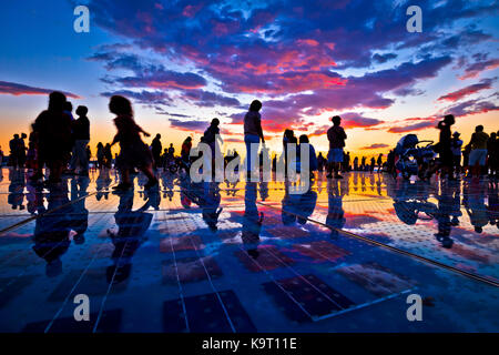 People silhouette on colorful sunset in Zadar, Dalmatia, Croatia - Stock Photo