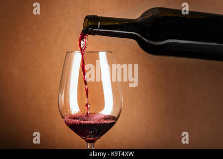 Red wine poured into glass from bottle - Stock Photo