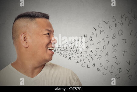 Side view portrait young handsome man talking with alphabet letters coming out of open mouth isolated grey wall - Stock Photo