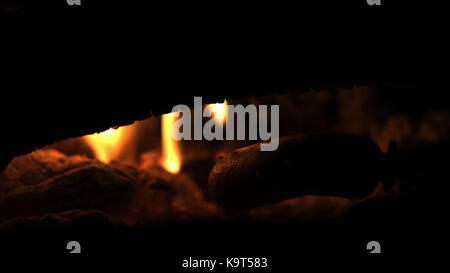 Making and cooking Hot dog sausages over open camp fire. Grilling food over flames of bonfire on wooden branch  - Stock Photo