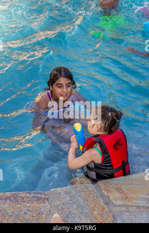 Two girls having a water gun fight stock photo 86108440 alamy for What is a freshwater swimming pool