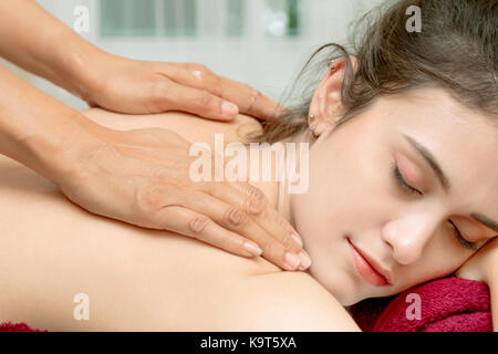 Close up of young woman getting spa treatment massage. Neck and back massage - Stock Photo