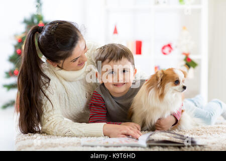 Happy family and the dog spending together Christmas time at home near the Christmas tree. New year concept - Stock Photo