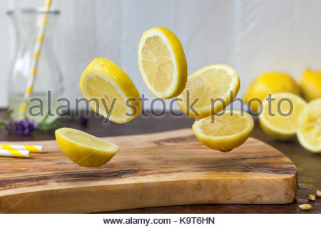 Lemon with flying pieces on a wooden board. Lemon lemonade with lavender and a striped yellow drinking straw in - Stock Photo