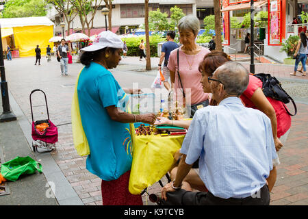 SINGAPORE - SEPTEMBER 7, 2017: A fortune teller practices chiromancy by reading the palm of a devotee outside the - Stock Photo