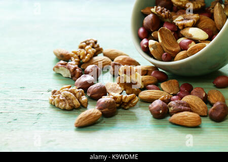 mix nuts - almonds, hazelnuts, peanuts, walnuts on a wooden background - Stock Photo