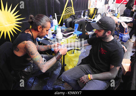 London, UK. 24th September, 2017. A tattooist at work at the the 13th London International Tattoo Convention, which - Stock Photo