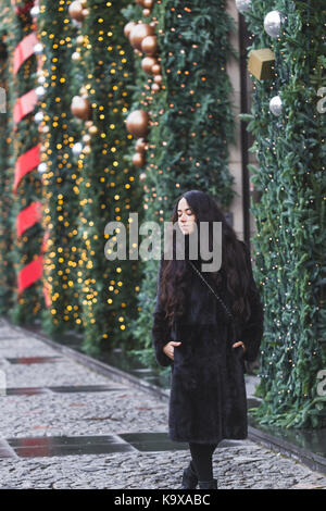 Happy woman walking in a black mink coat in city, beautifully decorated for the New Year - Stock Photo