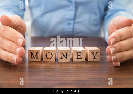 Businessperson Saving The Word Money Made From Alphabet Blocks - Stock Photo