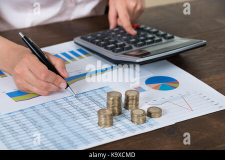 Close-up Of Businessperson With Stack Of Coins Over Graph And Report - Stock Photo
