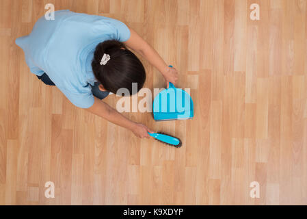 young woman brooming wooden floor with broom and dustpan stock photo