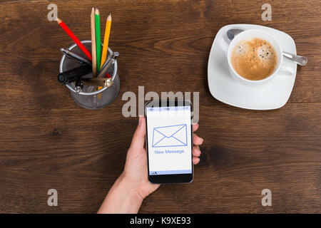 High Angle View Of Person Hand With Mobile Phone Showing New Message On Display - Stock Photo