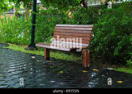 Bench made from wood beside at the park during rain drop - Stock Photo